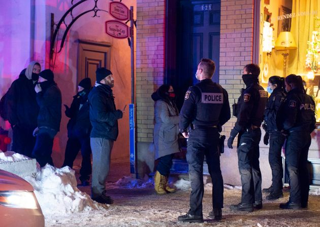 Quebec City police officers contain a handful of protestors as a curfew begins in the province to counter...