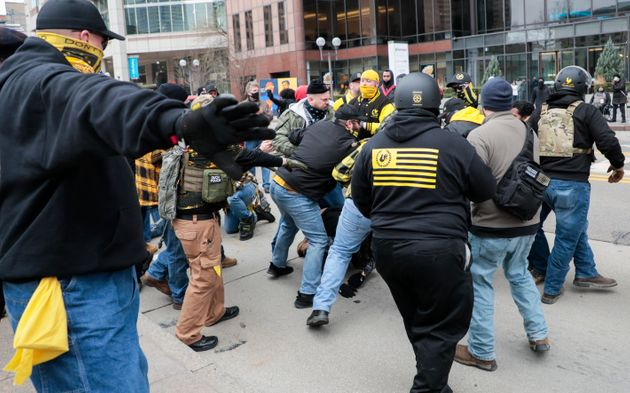 Members of the Proud Boys fight with a counter protester during a rally on Jan. 6, 2021, at the Ohio...