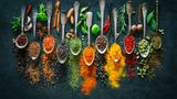 Colourful various herbs and spices for cooking on dark background