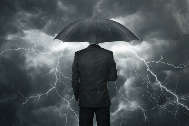Businessman with umbrella standing in the