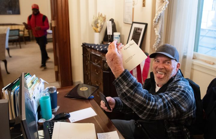 Trump supporter Richard Barnett holds a piece of mail as he sits inside the office of House Speaker Nancy Pelosi after protes