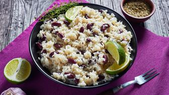 Caribbean Rice and Red Beans cooked with coconut milk seasoned with garlic, onions and creole spice in a bowl on a table mat on an old wooden table, view from above