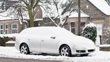 A snow covered car in front of a row of houses on the street in Edinburgh, Scotland.