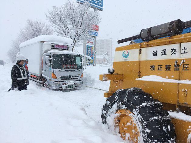 立ち往生が続く国道8号で、国土交通省の重機にけん引されるトラック(左)=2018年2月8日、福井市