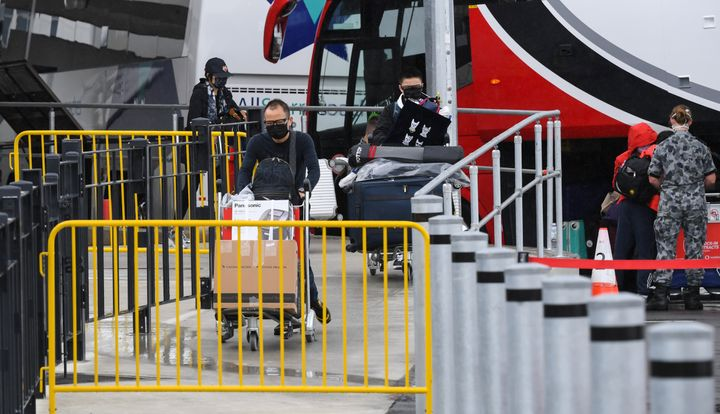 Passengers wearing face masks and face shields having recently landed from overseas walk to a hotel quarantine bus at Sydney International Airport on January 08, 2021 in Sydney, Australia.