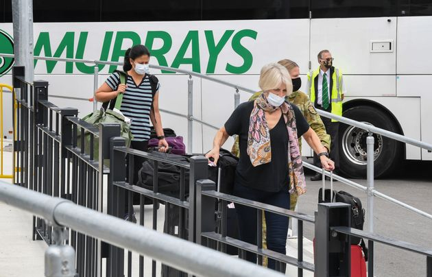 Passengers wearing face masks and face shields having recently landed from overseas walk to a hotel quarantine...