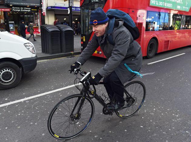 epa08932187 (FILE) - London Mayor Boris Johnson cycles along Oxford Street after attending an engagement...