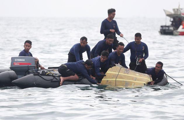 Des plongeurs de la marine indonésienne sortent une partie d'un avion de l'eau lors d'une opération...