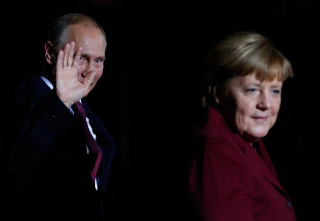 Russian President Vladimir Putin waves next to German Chancellor Angela Merkel as he arrives for talks...