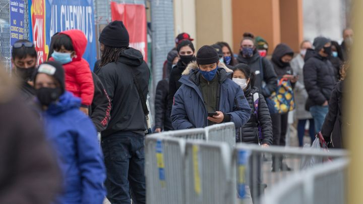 Shoppers line up outside a Scarborough, Ont., Walmart Superstore in this undated file photo. Ontario is defending its new rules designed to lower COVID-19 transmission amid criticism from some businesses.