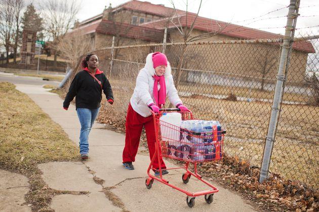 支給されたペットボトルをカートに乗せて運ぶヴァージニア・ミシェルさん(左)と義理の娘のティアラ・ウィリアムズさん(2016年2月22日)