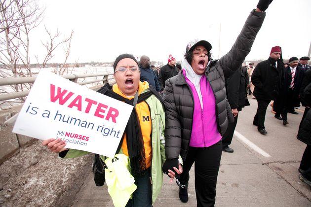 フリントの水質汚染問題に抗議する人々。手にしたカードには「水は人権」と書かれている(2016年2月19日)