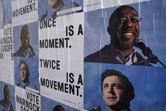 Campaign ads for Jon Ossoff and Raphael Warnock are seen on a wall near the John Lewis mural the day...