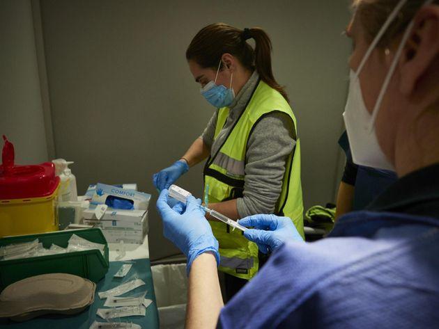 Dos trabajadoras sanitarias en un dispositivo para administrar la vacuna contra la