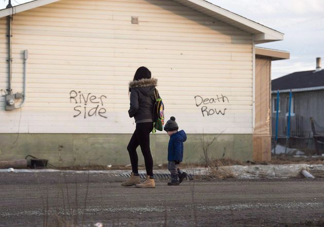 A woman and a child walk through the streets in Attawapiskat, Ont., on April 16,