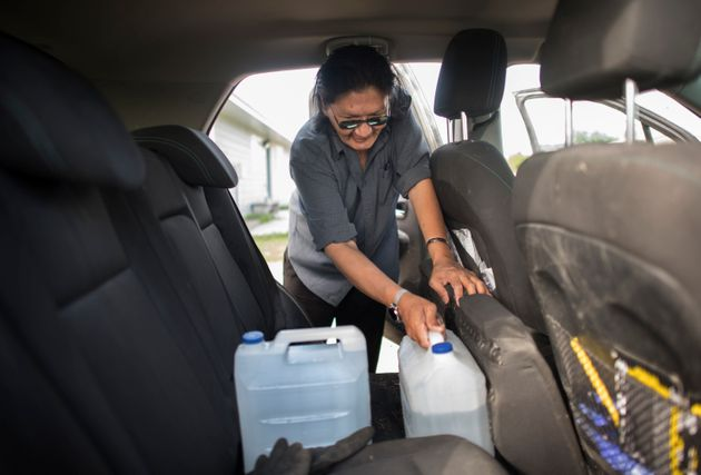 Norm Moonias fills his car with jugs of clean water in August 2019 as his home in the Neskantaga First...