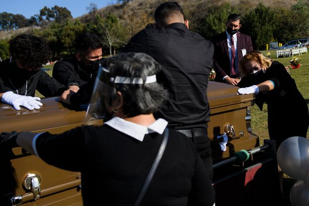 Family members mourn over the casket of Gilberto Arreguin Camacho, 58, who died from COVID-19, at a cemetery...