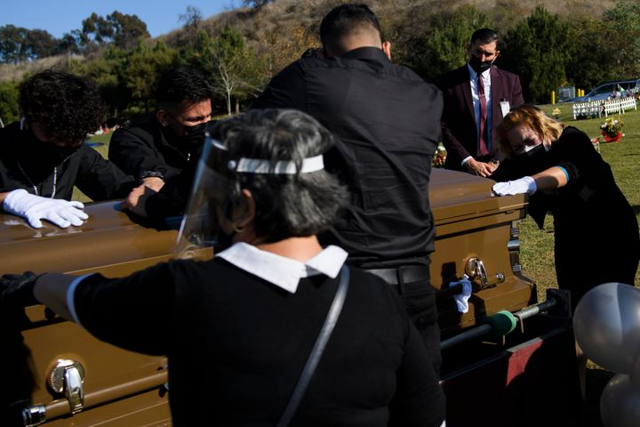 Family members mourn over the casket of Gilberto Arreguin Camacho, 58, who died from COVID-19, at a cemetery in Whittier, Cal