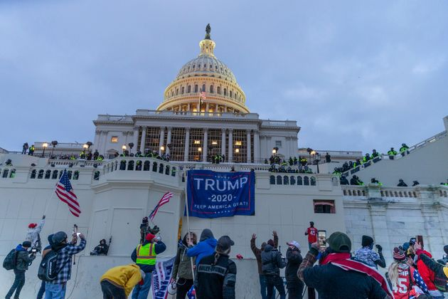 Insurrectionists hang Trump 2020 flags on the Capitol as they run rampant the