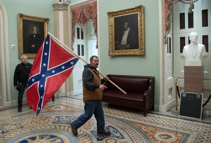 An insurrectionist parades the Confederate battle flag through the U.S. Capitol.