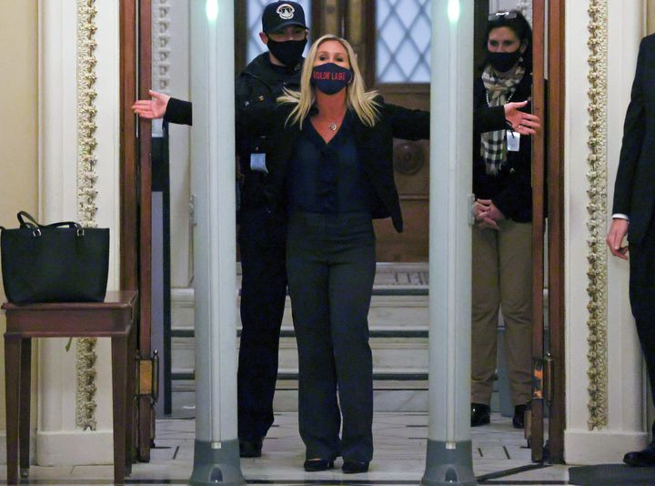 """Rep. Marjorie Taylor Greene (R-Ga), a QAnon conspiracy theorist, is searched outside the House chamber Tuesday night. Her mask says <em>molon labe</em>, a Greek phrase meaning """"come and take them"""" that the right wing uses as an anti-gun control slogan."""