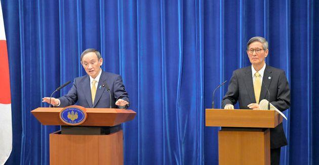 緊急事態宣言の区域変更で7府県追加を表明した後、記者会見で質問に答える菅義偉首相(左)。右は政府分科会の尾身茂会長=2021年1月13日午後7時39分、首相官邸、恵原弘太郎撮影