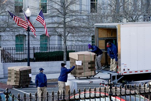 Workers unload pallets of unfolded boxes at the Executive Office Building on the White House grounds
