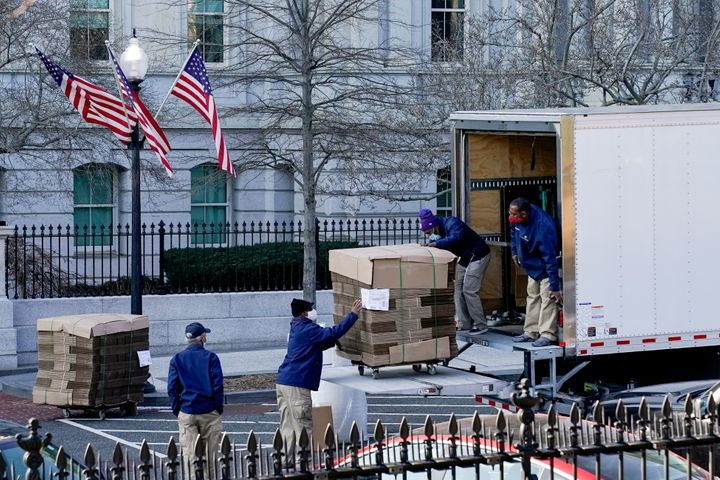 Workers unload pallets of unfolded boxes at the Executive Office Building on the White House grounds Wednesday.