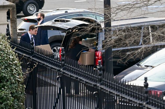 People load boxes and other items from the West Wing of the White House into a vehicle on