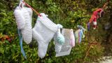 "Baby socks and hearts are pictured at a shrine in Tuam, County Galway in January 13, 2021, erected in memory of up to 800 children who were allegedly buried at the site of the former home for unmarried mothers run by nuns. - Irish prime minister Micheal Martin on Wednesday formally apologised for the treatment of unmarried women and their babies in state and church-run homes, where thousands of children died over decades. Some 9,000 children died in Ireland's ""mother and baby homes"", where unmarried mothers were routinely separated from their infant offspring, according to an official report published Tuesday. (Photo by Paul Faith / AFP) (Photo by PAUL FAITH/AFP via Getty Images)"