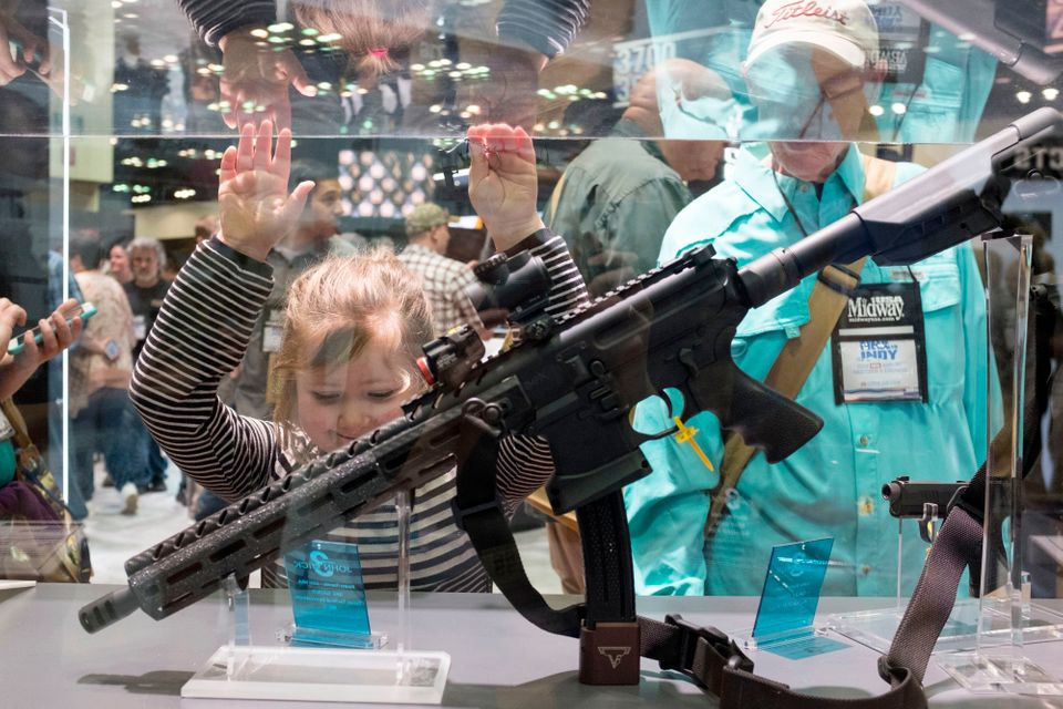 A young girl looks at the rifle was used in the upcoming movie