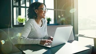 Smiling young African woman wearing glasses looking out of a window while sitting at a table working online with a laptop