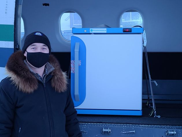 Arviat's Mayor Joe Savikataaq Jr. with the freezer containing hundreds of doses of the COVID-19 vaccine that were flown into the community on Jan. 13, 2021.