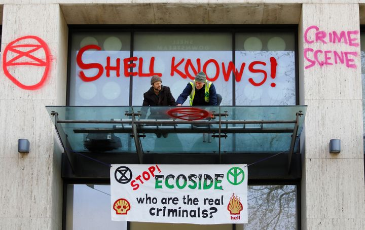 A climate activist sprays graffiti on the entrance to the Shell's British offices.