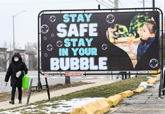A woman walks past a COVID-19 messaging sign during the COVID-19 pandemic in Mississauga, Ontario on...