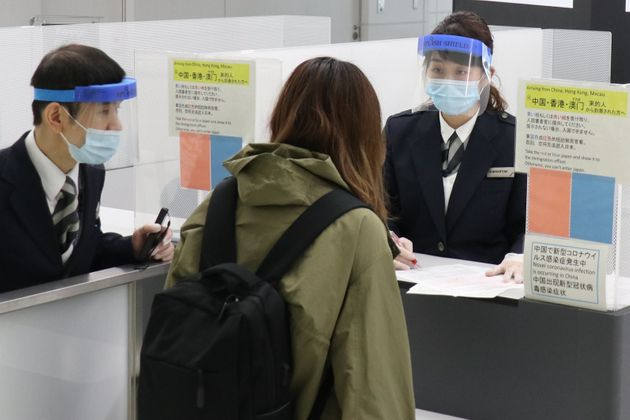 日本政府による米国からの入国制限発動で、検疫官とやり取りをする人=2020年3月26日、千葉・成田空港