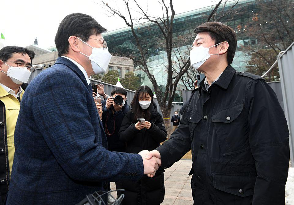 안철수 국민의당 대표가 15일 오전 서울 중구 서울시청 앞에 마련된 코로나19 임시 선별검사소에서 관계자와 인사하고 있다.