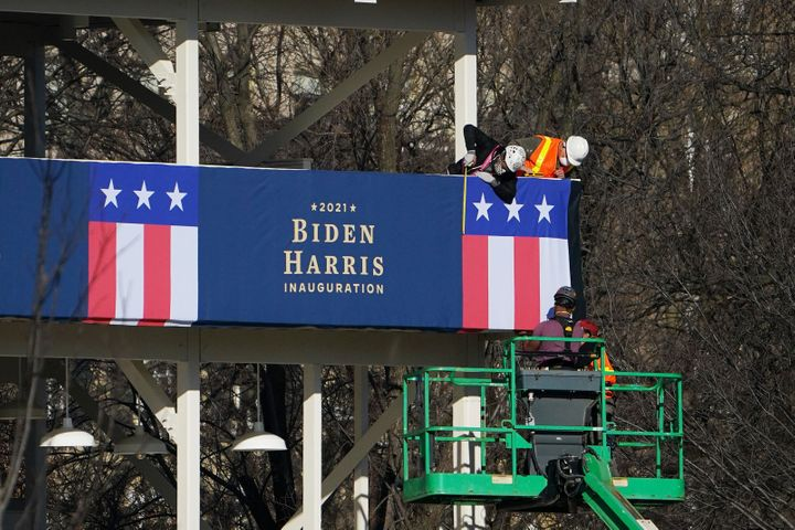 Workers adjust the bunting on a riser across from the White House on Thursday.