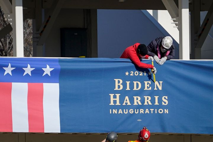 "Workers erect ""Biden-Harris"" bunting on a press riser Thursday along what would have been the inaugural parade route near the"