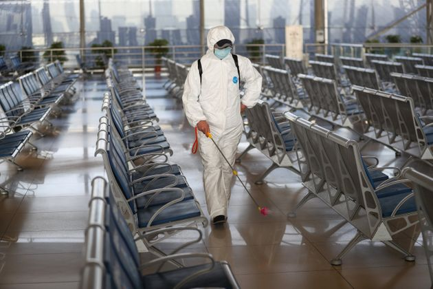 NANJING, CHINA - JANUARY 14: Staff member in protective suit sprays disinfectant at the waiting hall...
