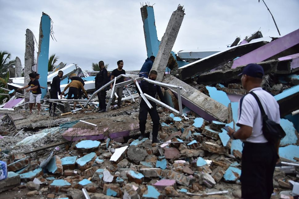 As many as 20 patients and staff are trapped beneath the rubble the Mitra Manakarra hospital in Mamuju city was flattened by