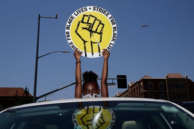 Foto de archivo del 20 de julio de 2020 de Audrey Reed, de 8 años, sosteniendo un letrero a través...