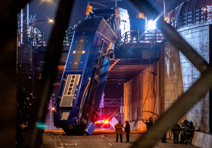 A bus in New York City which careened off a road in the Bronx neighborhood of New York is left dangling from an overpass on J