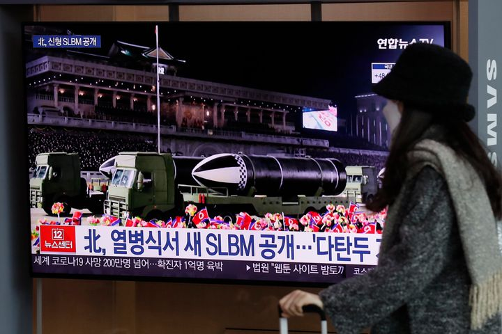 A woman wearing a face mask walks past in front of a TV screen showing a news program reporting about North Korea's military