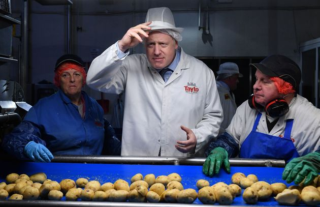 Boris Johnson helps quality control staff during a general election campaign visit to the Tayto Castle...