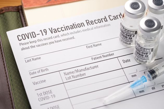 Covid-19 vaccination record card with vials and
