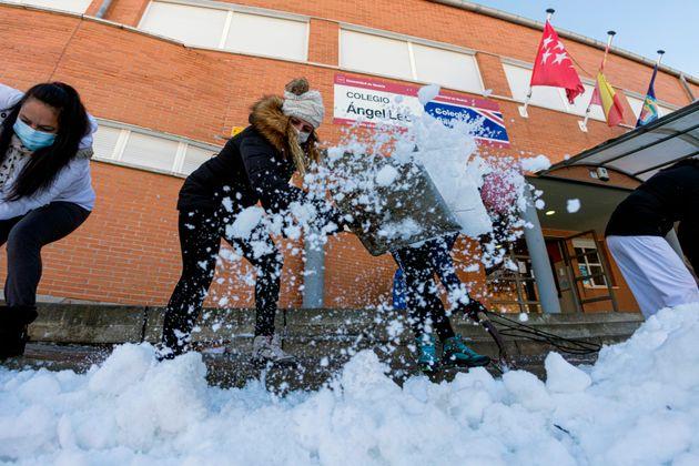 Personal de limpieza, madres y padres, trabajan este viernes en la retirada de hielo y nieve en un colegio...