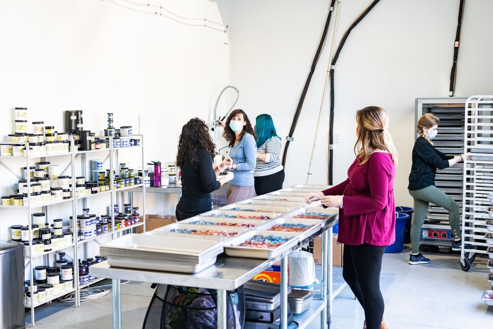 Sewrella employees work to dye yarn colorways in their new commercial space.