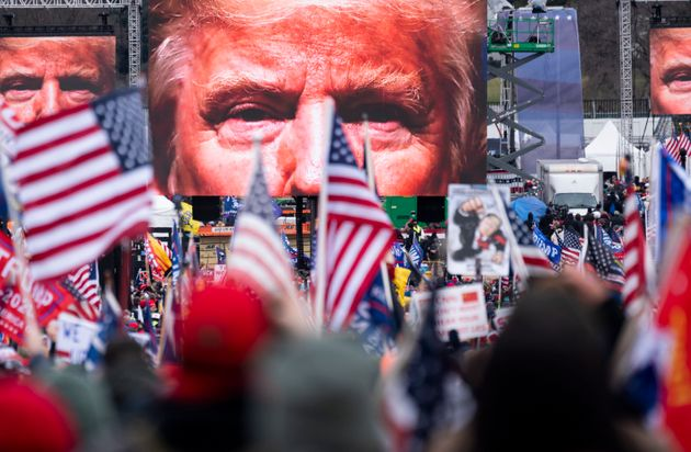 An image of President Donald Trump appears on video screens before his speech to his supporters on Jan....