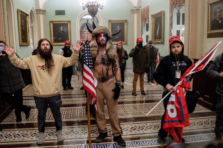 A lawyer for Jacob Chansley (center), the self-described Q Shaman, wants President Donald Trump to pardon his client because